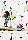 Various roses in vases on small table against fifties-style wallpaper