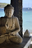 Stone Buddha statue on a wooden platform on the beach with an ocean view