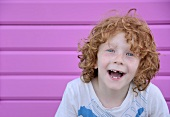 Laughing child in front of a pink wood wall