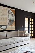 Naturfarbenes Polstersofa an schwarz getönter Wand mit modernem Bild neben Sprossentür