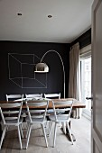 View through open door of white-painted kitchen chairs, rustic table, arc lamp and black-painted wall with drawing of cube