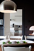 Designer pendant lamp with metal lampshade above dining table in front of open door with view into kitchen