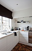 Corner of white, modern kitchen with white cupboards and integrated sinks below window with black Roman blind