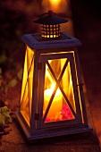 Laterne mit Kerze auf einem Gartenweg als abendliche Beleuchtung