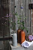 Milk thistles and globe thistles in rustic stoneware bottles and artichoke flowers arranged on pale blue cloth in front of old barn door