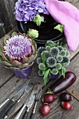 Globe thistles and artichoke flower arranged in ceramic pots next to aubergines, hydrangeas and pale violet cloth