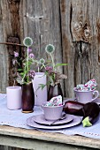 Posies of thistles and marjoram flowers in hollowed-out aubergines decorating table