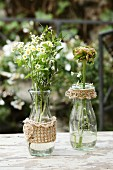 Glass bottles with hand-knitted covers and trims on table in garden