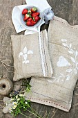 Hand-sewn hessian cushions on wooden table in garden