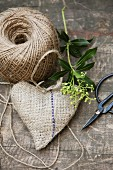 Still-life arrangement of hand-sewn, heart-shaped hessian sachet, reel of yarn and vintage scissors on wooden surface