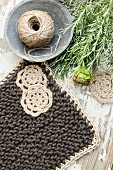 Pot holder hand-knitted from dark yarn bordered with pale jute yarn and decorated with small crocheted doilies