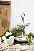 Hand-sewn hessian heart and crocheted doilies made from parcel string in front of chamomile on cake stand, white hydrangea and thyme in zinc pot