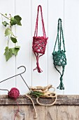 Lantern holders hand-crocheted from dyed jute yarn hanging on white wood panelling