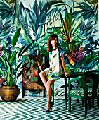Seated, smiling woman wearing summer dress in front of colourful, jungle-patterned wallpaper