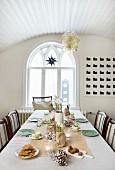 In zarten Farben weihnachtlich gedeckter Tisch; Esszimmer mit Glasballonlüster an gewölbter Holzdecke und Rundbogenfenster