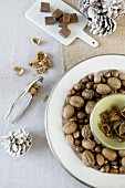 Festive table arrangement in natural shades with nuts on pale plates with silver rims, squares of chocolate on china board and white fir cones