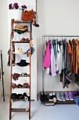 Alte Holzleiter als Ablage für Damenaccessoires; daneben ein Kleiderständer aus Metallrohren mit daran hängender Kleidung