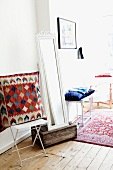 Large 'ethnic' pillow on a white metal folding chair; next to it a full length mirror leaning on a old wooden box