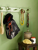Green bathroom wall with wooden wall coat rack with jewelry hanging from it and a homemade fabric tote bag; underneath an antique side table