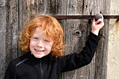 Red haired child in front of a wooden door