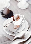 Ostergedeck mit Vogelfedern in Tasse