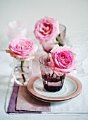 Pink roses in glasses decorating table