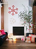 Interior with fireplace festively decorated with snowflakes on wall & wrapped Christmas presents