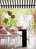 Flower arrangements suspended over festively decorated table and chairs