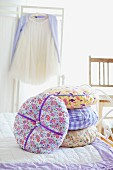 Stack of scatter cushions on bed in bedroom
