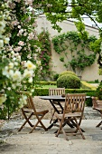 Garden table and chairs amongst roses and box hedges