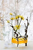 Arrangement in jar: cornelian cherry blossom and pussy willow with willow catkins held to outside of jar with washi tape