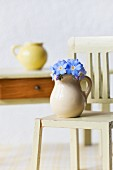 A few forget-me-not flowers in tiny jug on dolls' house chair in front of small wooden table