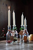 Candles and plant materials in bottles with numbered tags