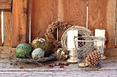 Advent arrangement of decorative spheres and wire basket of fir cones in front of candles and hand-made wreaths leaning on wooden wall