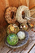 Advent arrangement of decorative spheres and hand-crafted wreaths on weathered wooden boards and leaning against wooden wall