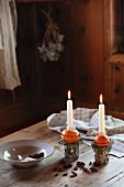 Hand-crafted candlesticks made from oranges stuck with cloves and dish on wooden table in festive, log-cabin atmosphere