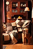 Candle lantern with knitted cover on tree trunk stool in front of comfortable armchair with knitted patchwork scatter cushions and antique dresser against wooden wall