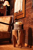 Candle lantern with knitted cover on tree trunk stool in front of comfortable armchair in wooden chalet