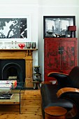 Black leather couch and glass table in front of open fireplace and red-painted, Oriental cabinet in traditional living room