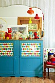 Blue-painted, half-height cabinet with printed paper behind glass door panels in child's bedroom