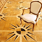 Rokoko Stuhl auf Parkettboden mit Windrosen-Motiv als Intarsie