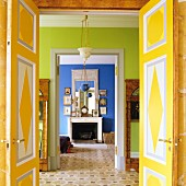 Open, colourfully painted double doors and view through green anteroom into blue interior with open fireplace