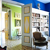 Rococo armchair in front of fitted bookshelves in blue interior; view into green room through open double doors in grand house