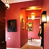 Red-painted hallway with gallery of ancestral portraits
