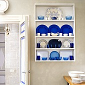 Blue and white crockery in wall-mounted shelves next to open door