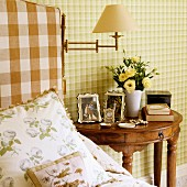 Scatter cushions on bed next to antique, semi-circular bedside table in exotic wood against wall with green checked wallpaper