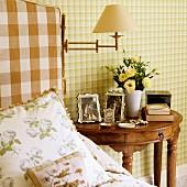 Kissen auf Bett neben antikem, halbkreisförmigen Nachttisch aus Edelholz vor Wand mit grüner Karo-Tapete