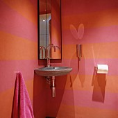 Stone corner washbasin and mirrored cabinet in pink and orange striped guest toilet