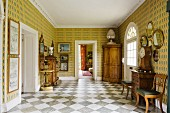 Spacious foyer with antique, 18th century furniture, boldly patterned wallpaper and diagonal, chequered marble floor tiles