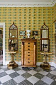 Antique chest of drawers flanked by small marble tables and decorative mirrors on patterned wallpaper in foyer of English country house with marble-tiled floor